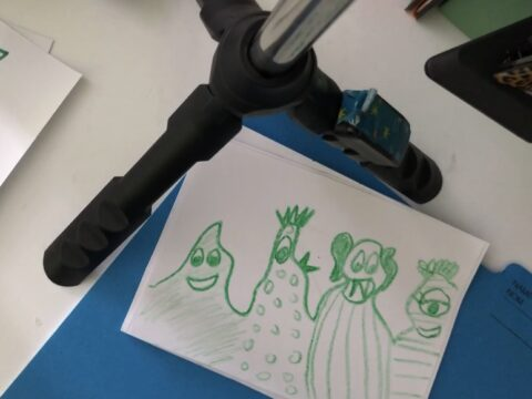 a drawing of 4 green monsters on an index card