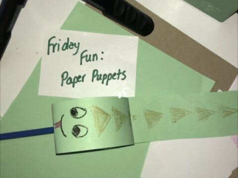 a green snake puppet made of paper in front of a sign that says 'Friday Fun Paper Puppets'