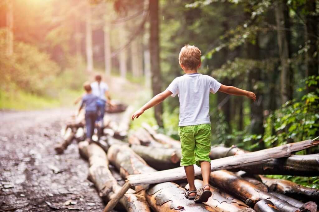Photo of children walking on logs in the forest.